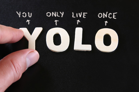 millennial: man hand pointing at the words YOLO you only live once written on black leather background Stock Photo
