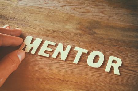 männliche Hand das Wort Mentor aus Holzbuchstaben über Holztisch Hintergrund Rechtschreibung. Retro-Stil Bild