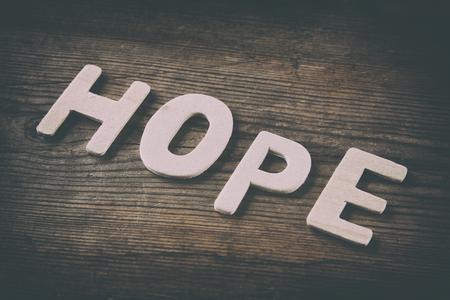 zdrowie: Słowo HOPE wykonane z bloków drewnianych literami na tle drewnianych. rocznik filtrowane i stonowanych