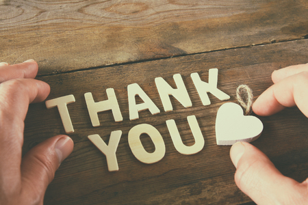 dziękuję litery i męską rękę nad drewnianym stole. rocznik filtrowane i stonowanych