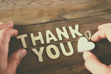merci: lettres de remerciement et la main de l'homme sur la table en bois. cru filtr� et tonique