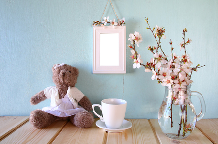 blank photo: cute teddy bear, cup of coffee and blank frame next to spring white cherry blossoms tree