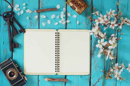 春の白い桜の木のイメージの表示は、空白のノートブック、青い木製のテーブルで古いカメラを開く