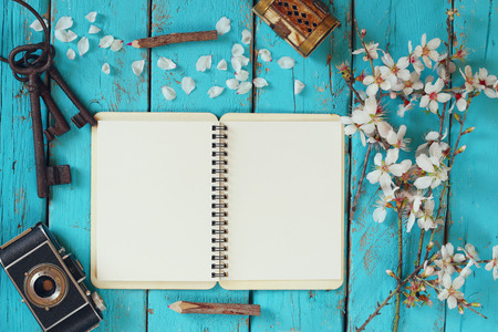 note book: top view image of spring white cherry blossoms tree, open blank notebook, old camera on blue wooden table