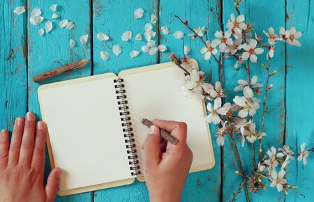 person writing: woman writing on blank notebook next to spring white cherry blossoms tree on vintage wooden table. Stock Photo