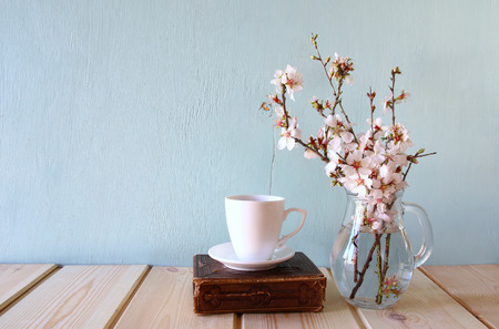 old book, cup of coffee next to spring white flowers on wooden texture Stock Photo