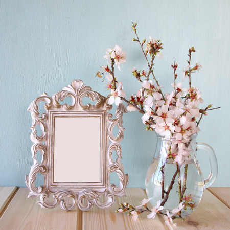 table decoration: vintage blank frame next to white spring flowers. selective focus. template, ready to put photography Stock Photo