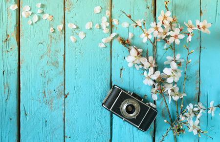 widok z góry obraz wiosny białe kwiaty wiśni drzewa obok starego aparatu na niebieskim drewnianym stole