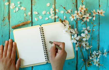 woman writing on blank notebook next to spring white cherry blossoms tree on vintage wooden table. Stock Photo