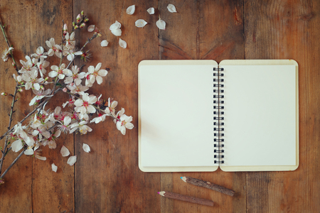top view image of spring white cherry blossoms tree next open blank notebook on wooden table. vintage filtered and toned image Stock Photo