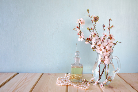 fresh vintage perfume bottle next to white spring flowers on wooden table