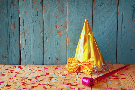 party hat next to pink party whistle on wooden table with colorful confetti. vintage filtered image