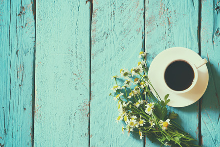 sunny day: top view image of daisy flowers next to cup of coffee on blue wooden table. vintage filtered