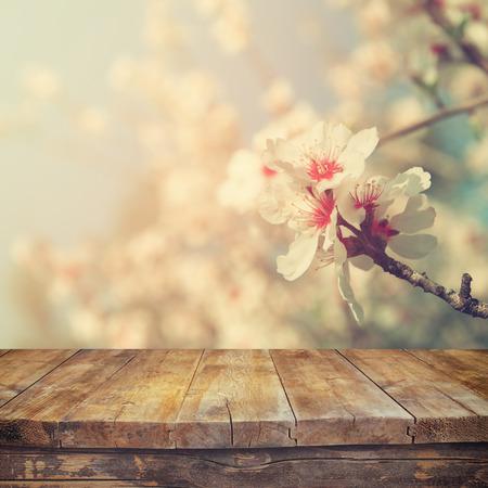 houten rustieke tafel in de voorkant van de lente witte kersenbloesem boom. vintage gefilterde afbeelding. product-display en picknick-concept Stockfoto
