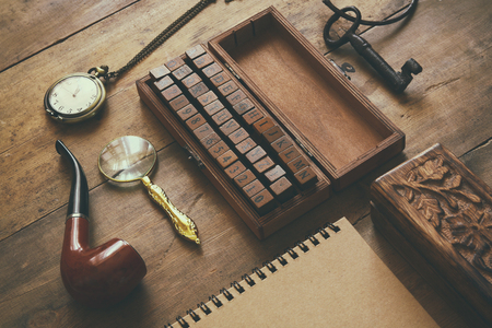 sherlock: detective concept. Private Detective tools: magnifier glass, old keys, smoking pipe, notebook. top view. vintage filtered image