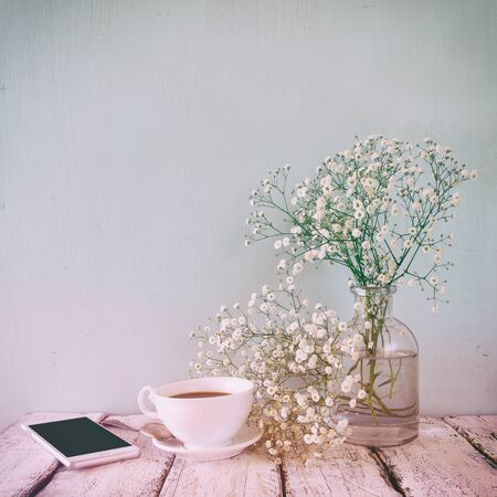caffee: vintage filtered and toned image of smart phone, cup of coffee next to spring white flowers Stock Photo
