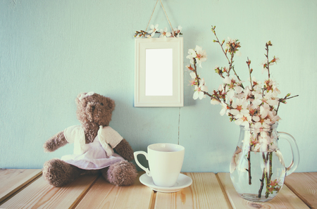 photo frame: vintage filtered and toned image of cute teddy bear, cup of coffee and blank frame next to spring white cherry blossoms tree