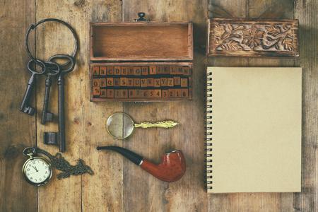 concept de détective. outils de détective privé: verre de loupe, vieilles clés, pipe, bloc-notes. vue de dessus. image vintage filtrée