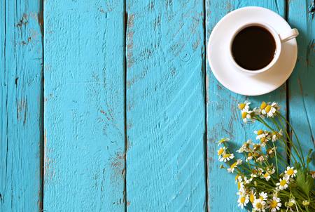 bovenaanzicht beeld van daisy bloemen naast kopje koffie op blauwe houten tafel Stockfoto