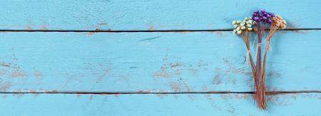 古い青い木製の背景にカラフルなドライフラワーのウェブサイト バナーの背景 写真素材