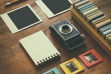 bovenaanzicht van vintage camera en oude dia's frames over houten tafel achtergrond