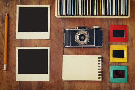 top view of vintage camera and old slides frames over wooden table background
