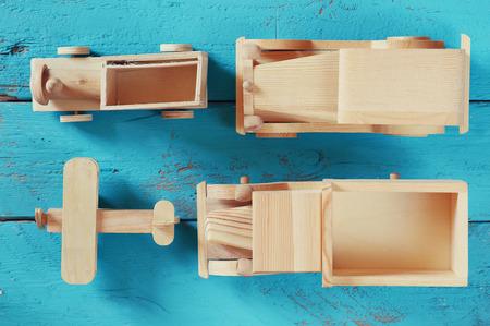 juguetes de madera: viejos juguetes de madera de transporte: tren, coche, avión de la pista y en el fondo de madera azul. la vendimia se filtró y tonificado