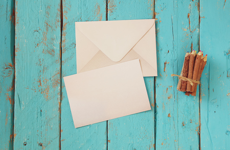 carta de amor: top view image of blank letter paper and envelope next to colorful pencils on wooden table. vintage filtered and toned