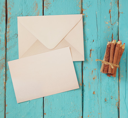 love letter: top view image of blank letter paper and envelope next to colorful pencils on wooden table. vintage filtered and toned