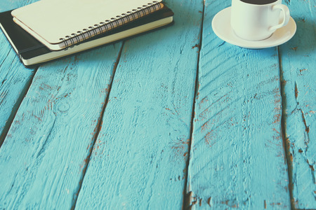 top view image of blank notebook next to cup of coffee