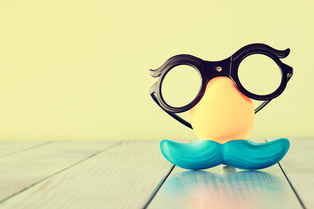 fanny: fanny glasses and moustache mask on wooden table. retro filtered
