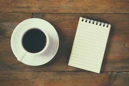 sol: Imagen de la visión superior de cuaderno en blanco junto a la taza de café. la vendimia se filtró y tonificado Foto de archivo