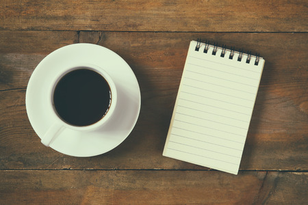 top view image of blank notebook next to cup of coffee. vintage filtered and toned Stock Photo