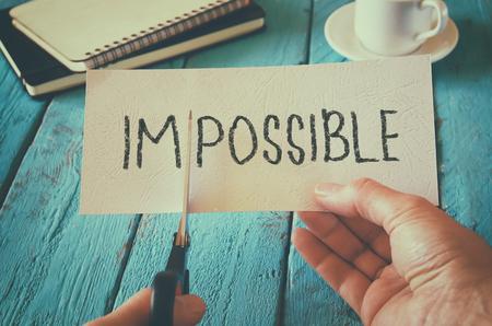 Mann Hand hält Karte mit dem Text unmöglich, Schneiden Sie das Wort im so kann geschrieben. Erfolg und Herausforderung Konzept. Retro-Stil Bild