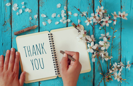 woman hand writing a note with the text thank you on a notebook, over wooden table and cherry blossom flowers 스톡 콘텐츠