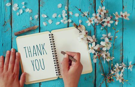 Kobieta strony pisania notatki z tekstem dziękuję na notebooku, nad drewnianym stołem i wiśni kwiat kwiaty
