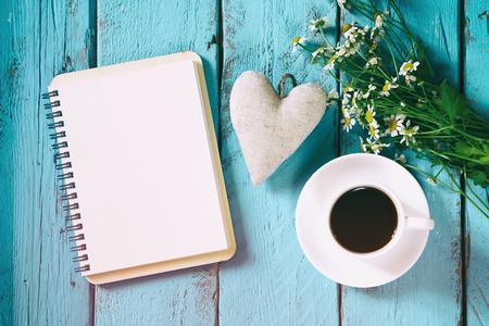 Cosecha filtrada y tonificada imagen de vista superior de flores de margarita, bloc de notas en blanco y tejido de corazón junto a la taza de café en la mesa de madera azul. Vintage filtrada y tonificada Foto de archivo