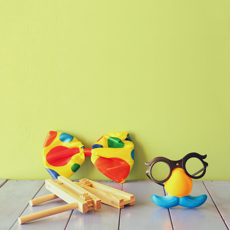 purim: fanny glasses with mustache mask and noisemaker toy on wooden table. selective focus Stock Photo