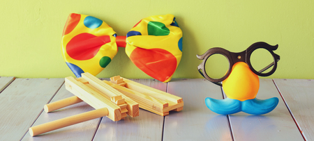 noisemaker: fanny glasses with mustache mask and noisemaker toy on wooden table. selective focus Stock Photo