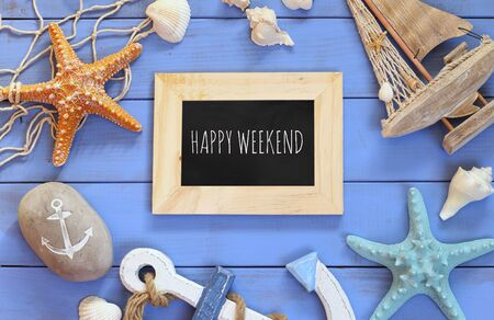 top view of nautical concept with chalkboard and text: HAPPY WEEKEND next to nautical life style objects