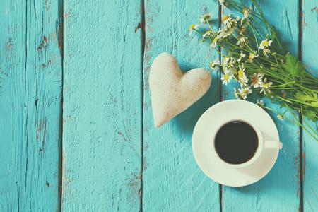 Bild Draufsicht von Daisy Blumen und Stoffherz neben Tasse Kaffee auf blauem Holztisch. Jahrgang gefiltert und getönten