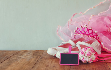 party outfit: Small girls party outfit: white shoes, crown and wand flowers on wooden table. bridesmaid or fairy costume