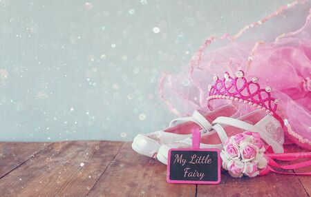 cinderella dress: Small girls party outfit: white shoes, crown and wand flowers next to small chalkboards with phrase MY LITTLE FAIRY: on wooden table. bridesmaid or fairy costume. glitter overlay