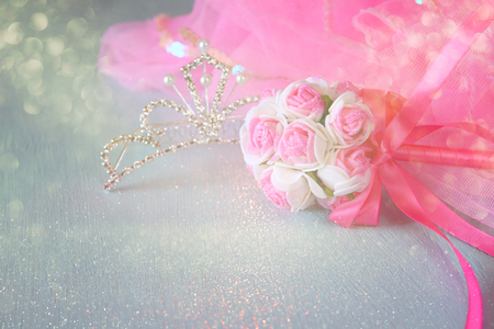 party outfit: Small girls party outfit: crown and wand flowers on wooden table. bridesmaid or fairy costume. glitter overlay