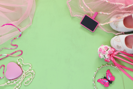 party outfit: top view of Small girls party outfit: white shoes, crown and wand flowers next to small chalkboard. bridesmaid or fairy costume Stock Photo