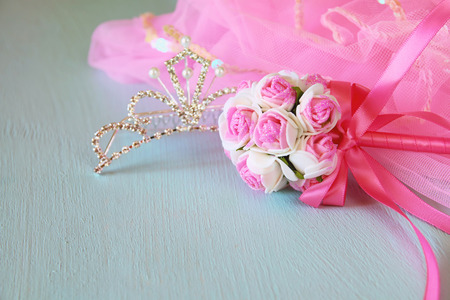 party outfit: Small girls party outfit: crown and wand flowers on wooden table. bridesmaid or fairy costume. selective focus Stock Photo