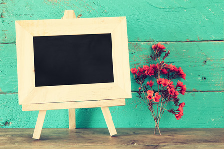 photo frame: blank blackboard next to flowers on wooden table. vintage filtered