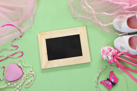 party outfit: top view of Small girls party outfit: white shoes, crown and wand flowers next to chalkboard. bridesmaid or fairy costume