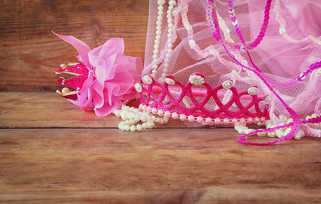 party outfit: Small girls party outfit: crown and vail on wooden table. bridesmaid or fairy costume