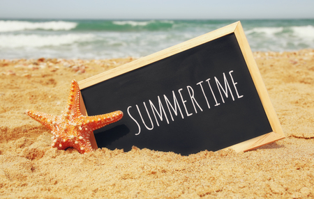 starfish and clachboard with phrase: SUMMERTIME, on sea sand and ocean horizon Stockfoto